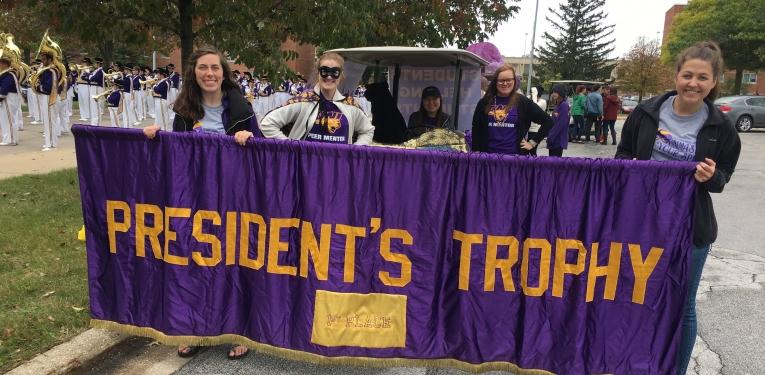 Peer mentors holding President's Trophy banner